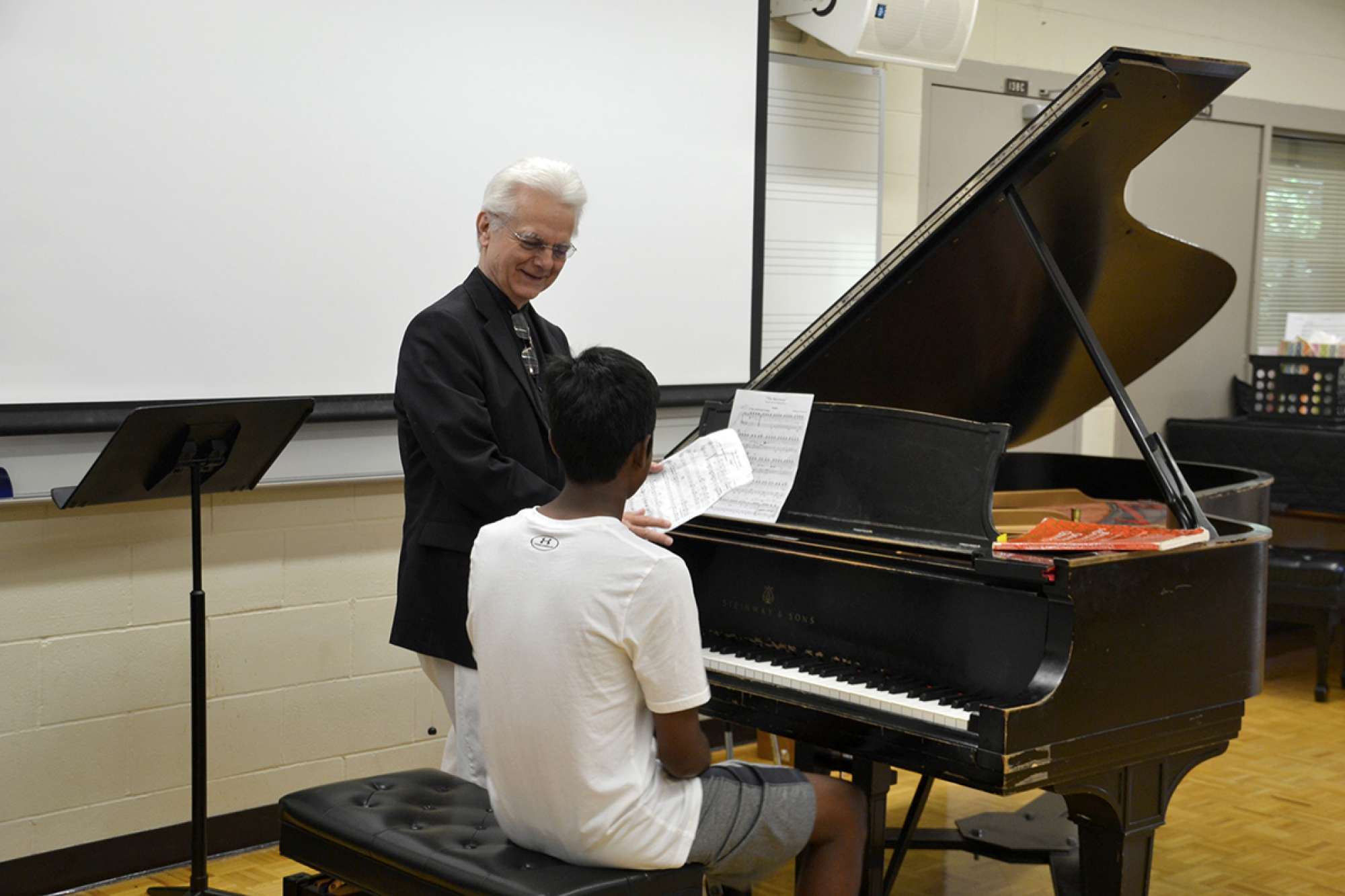 Piano instructor and student at a piano