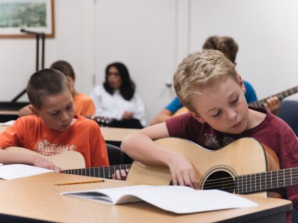 Group of students learning to play guitar