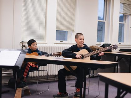 Two students learning to play guitar
