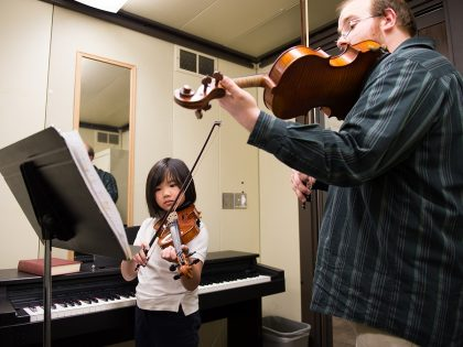 Instructor and student playing violin