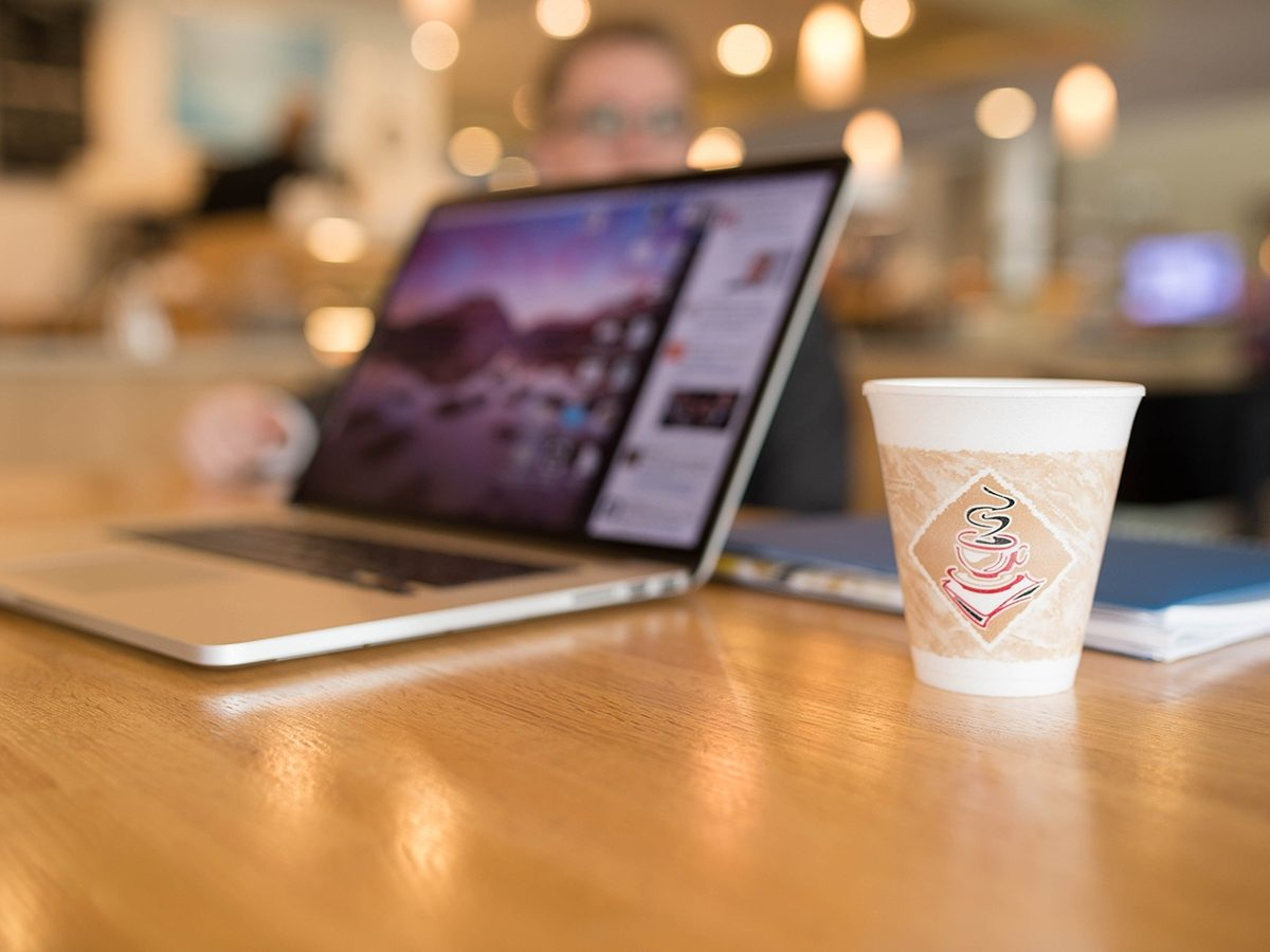Laptop and coffee cup on table