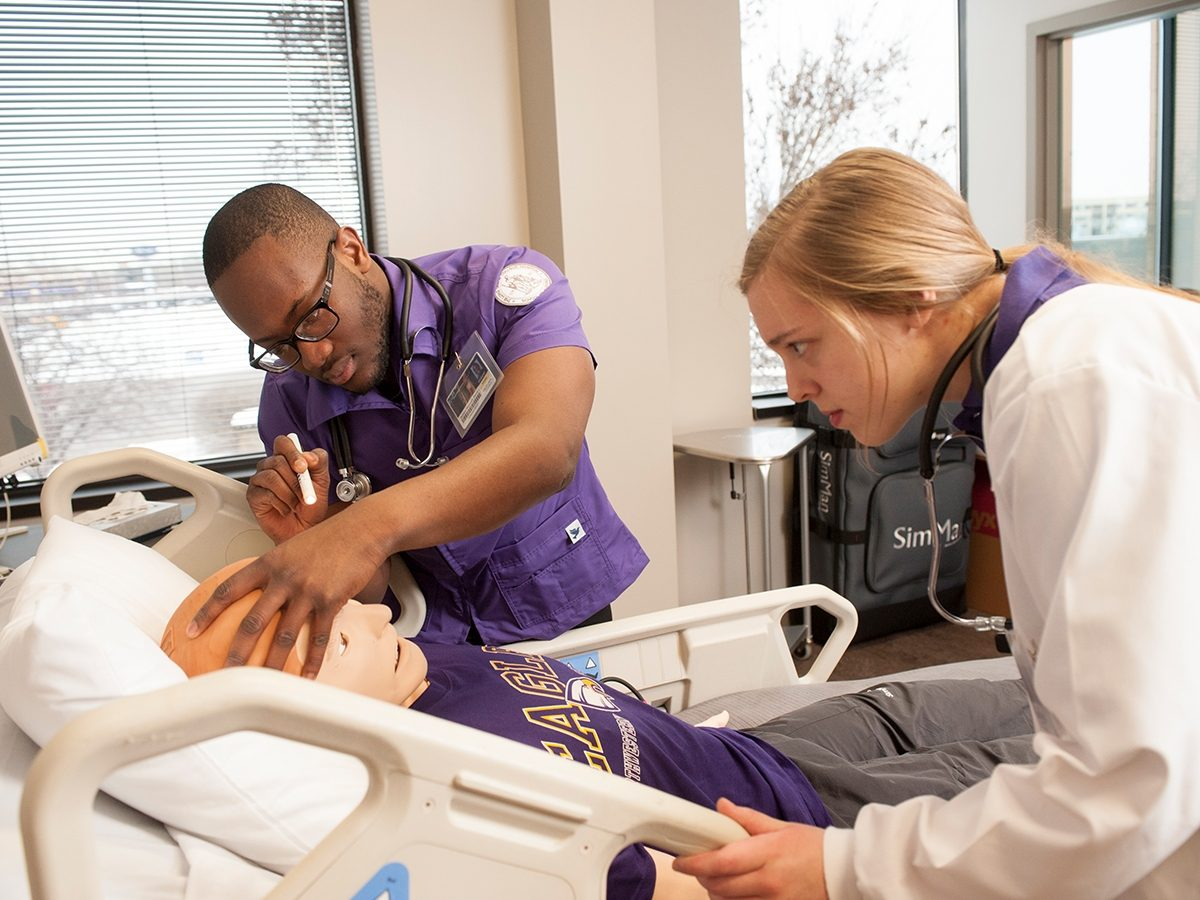 Nursing students practicing with a mannequin