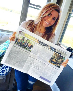 Ashely holding a copy of Northwestern's student newspaper The Examiner paper