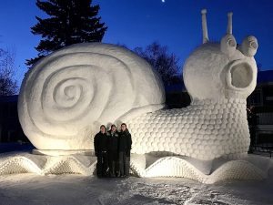 Bartz Brothers in front of snow sculpture Slinky the Snail.