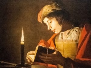 Person reading by candle light