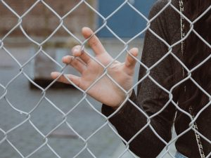 Teenage girl standing behind fence
