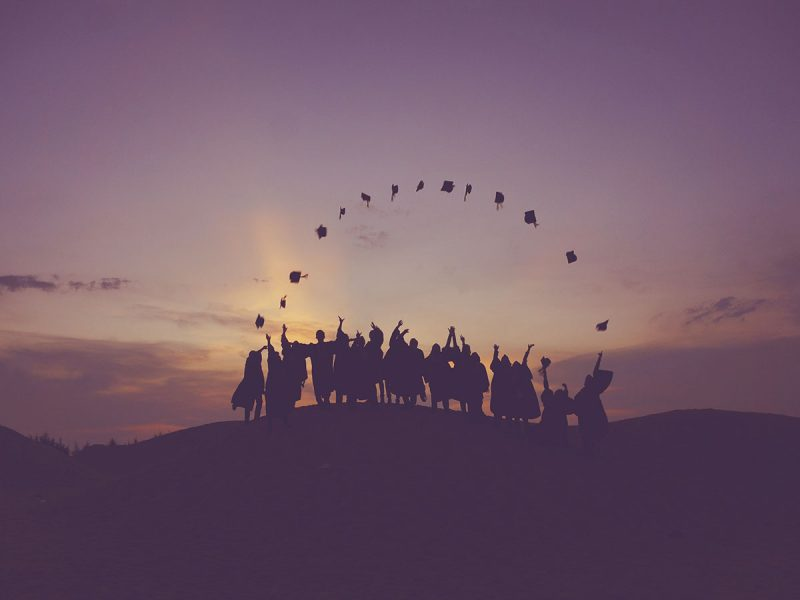 Graduates throwing their hats in the sunset