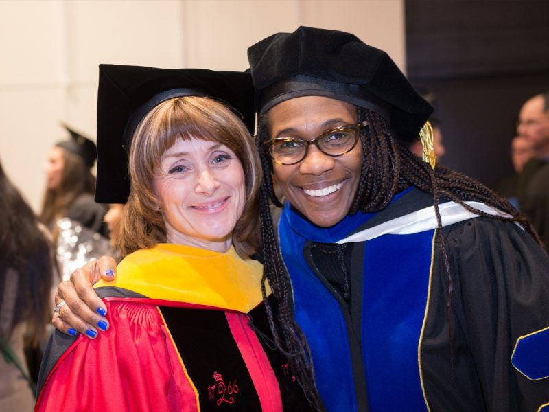Two professors wearing their cap and gown