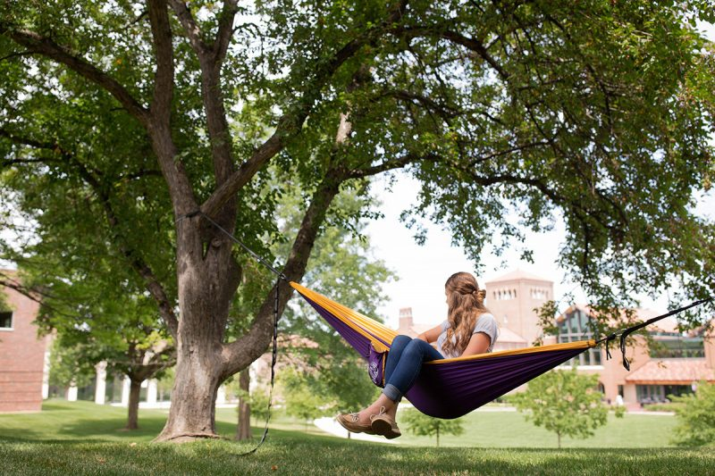student sitting outside in a hammock