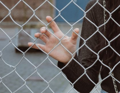 Teenage girl standing behind fence