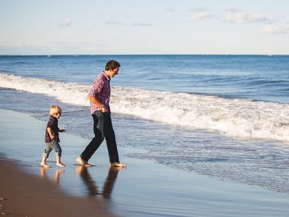 father and son on the beach walking towards the water