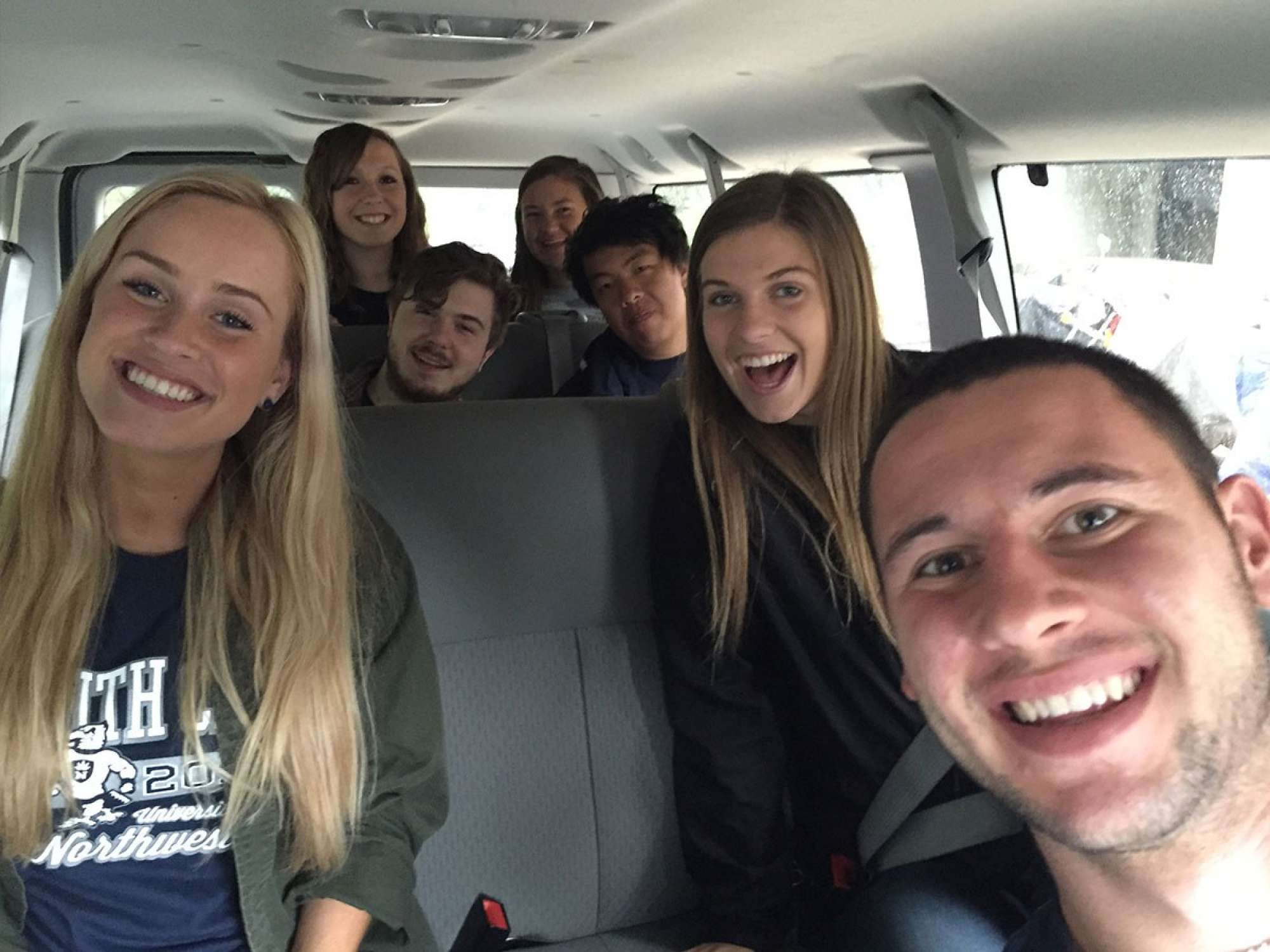 Group of diverse Northwestern Youth Crew member riding in a shuttle van.
