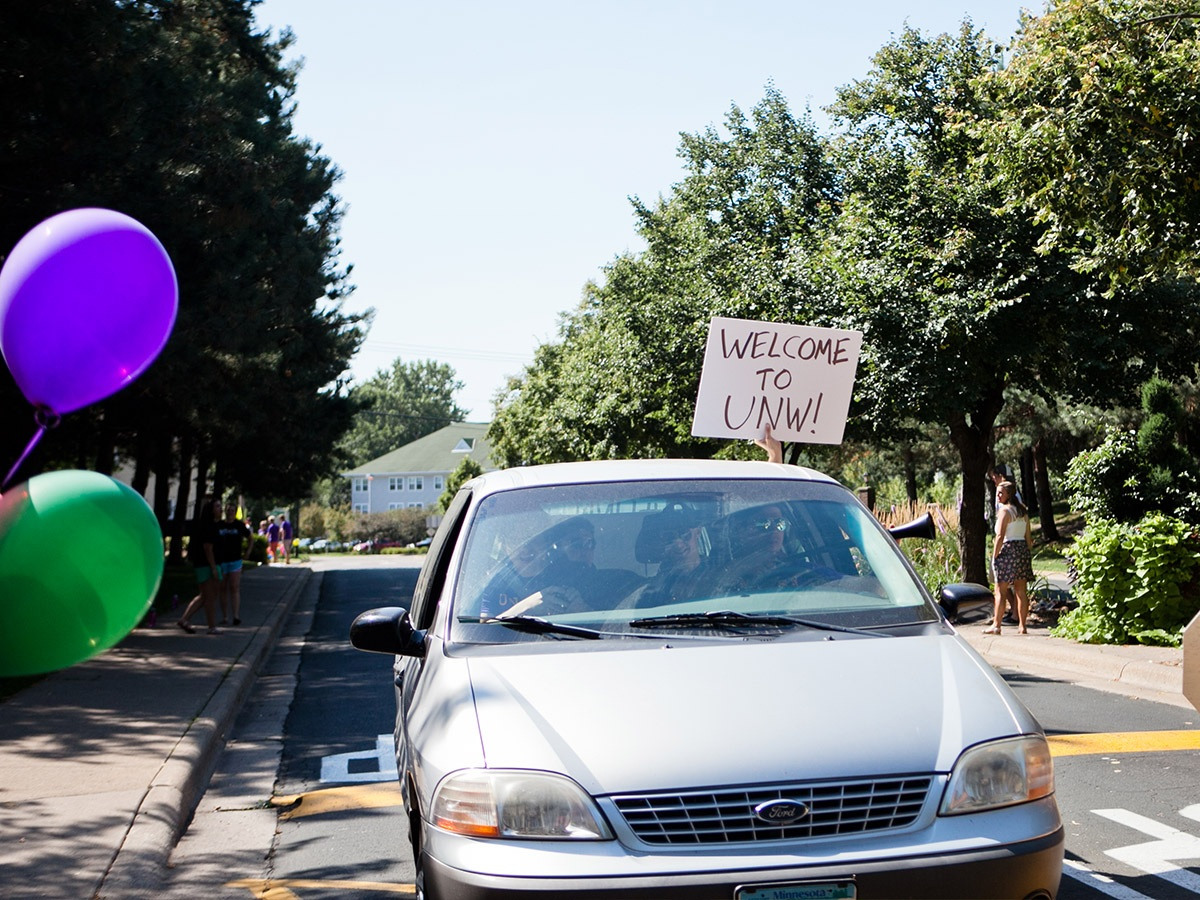 "commuters in a car holding sign that says ""welcome to UNW"""