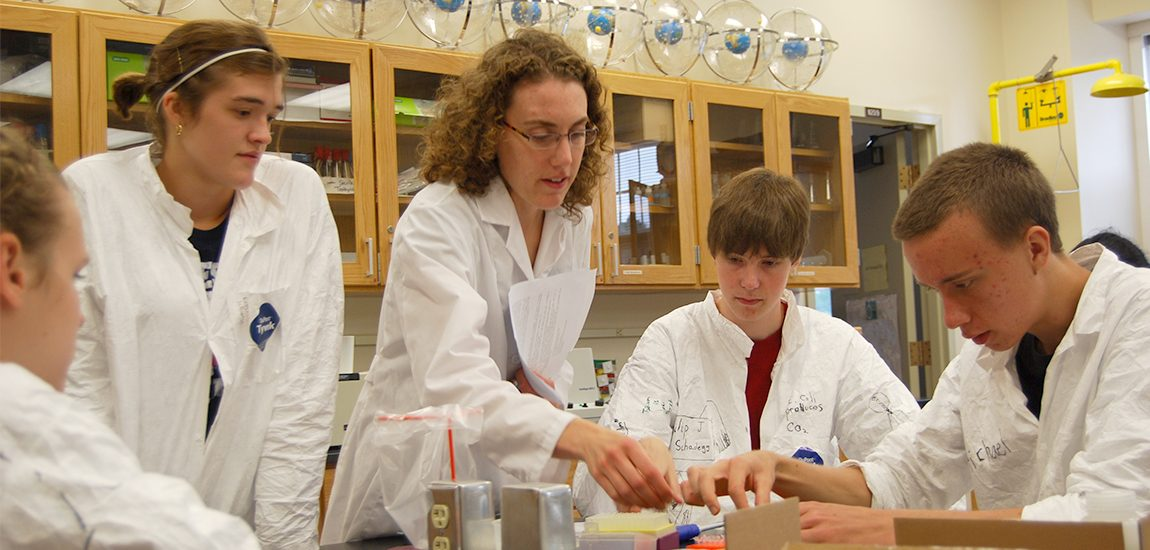 Professor giving instructing students in a biochemistry lab