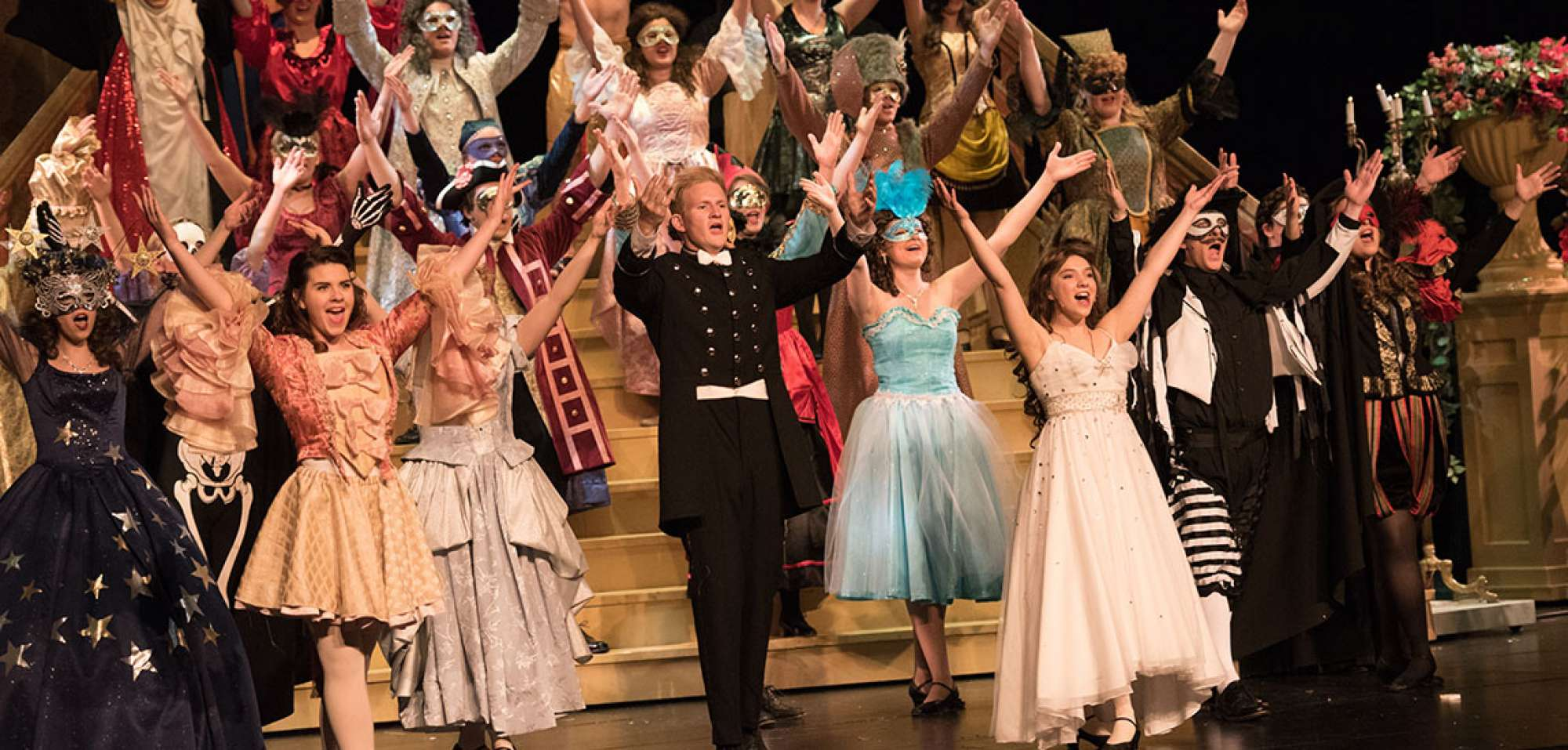Costumed cast with arms raised in the grand finale of a musical number