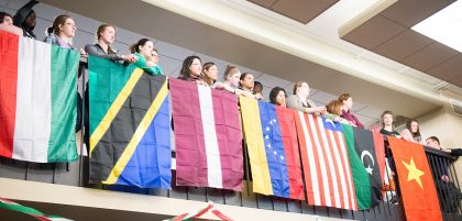 Students gathered by flags hanging on a banister