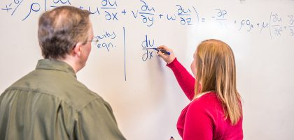 Student and professor working on white board