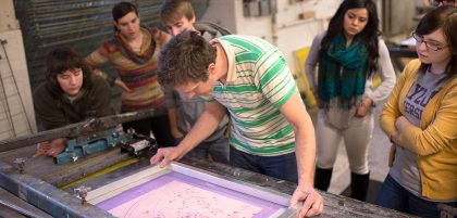 Students watch a professor give an art tutorial
