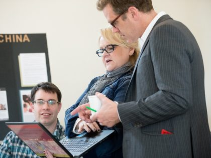 Three faculty looking at laptop screen