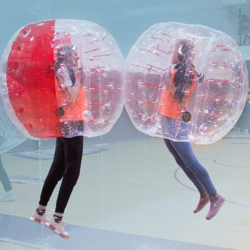 two students playing inside of gym with bubble balls