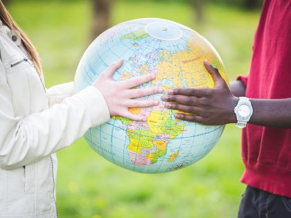 Two people holding a globe together