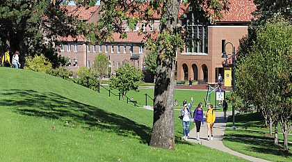 students walking on the sidewalk of campus