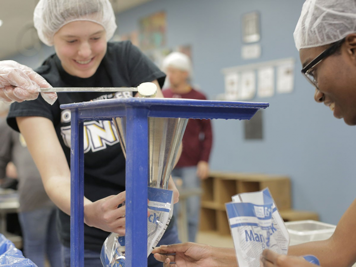 Northwestern students volunteering at Feed My Starving Children packing meals