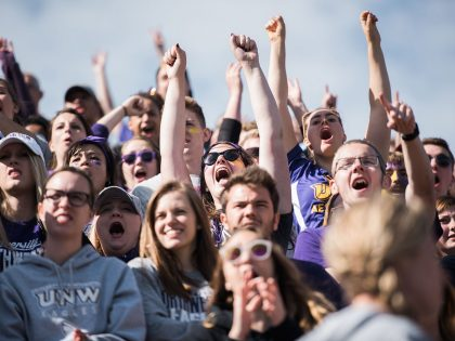 Northwestern students and alumni cheering at a homecoming football game.