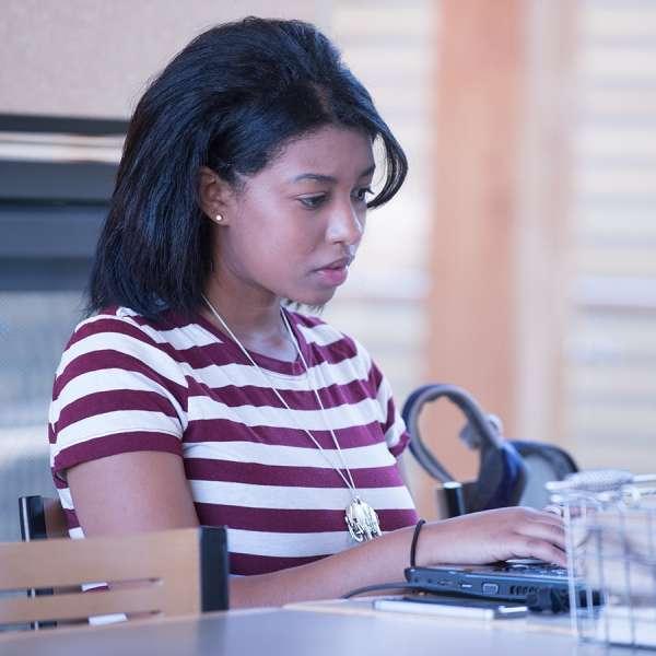Student on laptop near fireplace