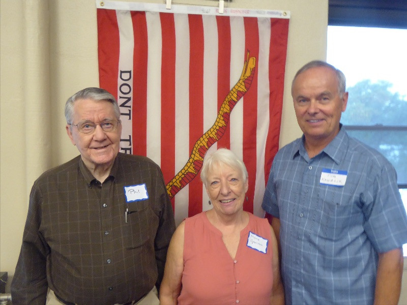 Two men and a woman standing in front of a flag