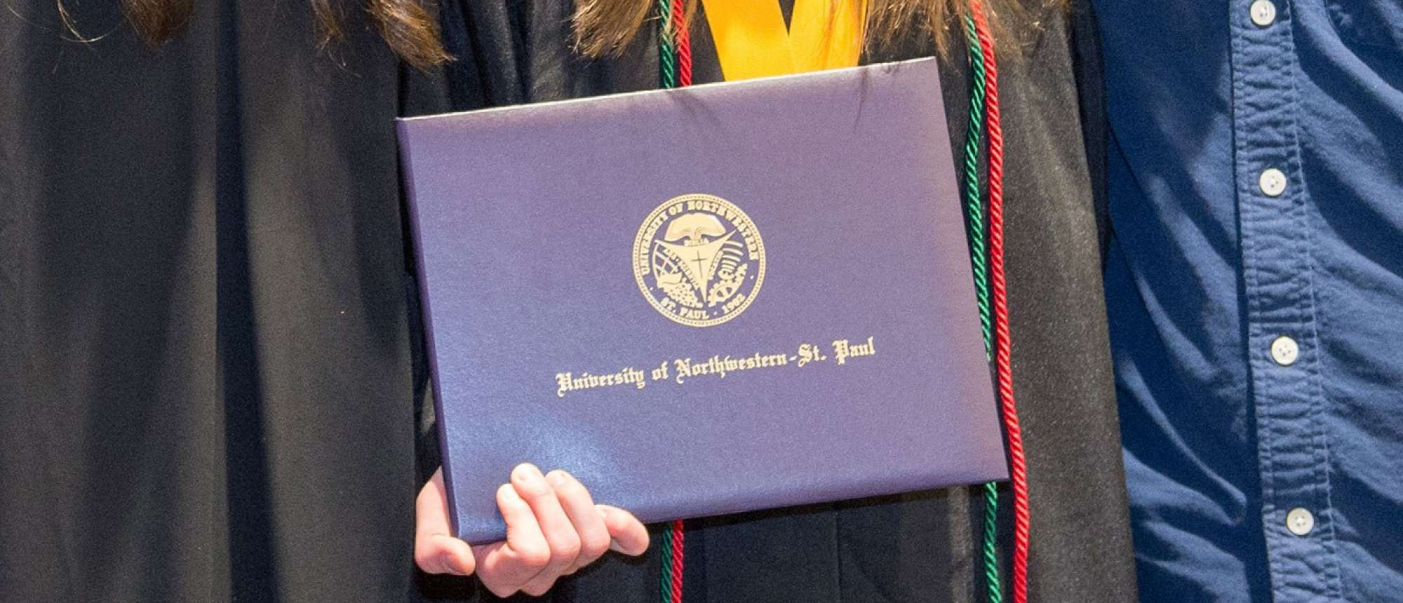 Graduate holding her degree certificate.