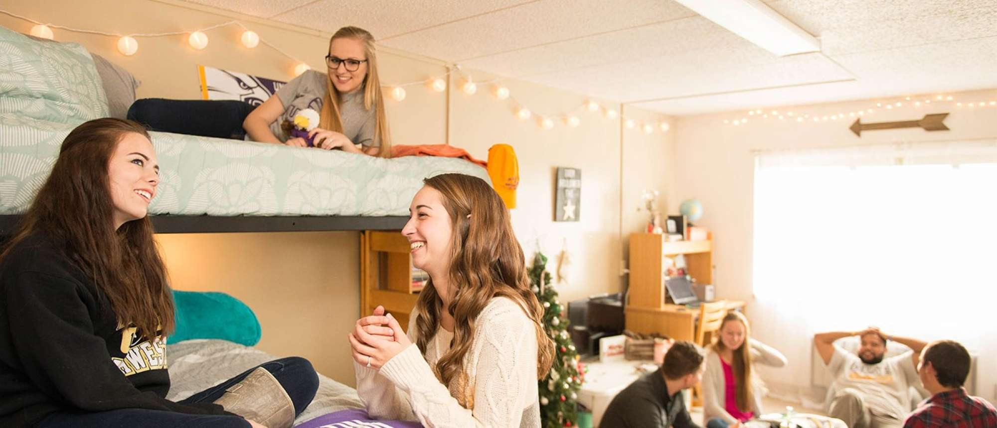 Students hanging out together in dorm room.