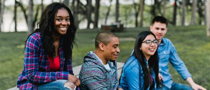 Photo of diverse students along the campus lake shore.