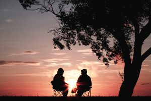 Silhoutte of two people watching a sunset