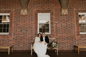 Newly-married couple sitting on bench in front of Northwestern's Nazareth Hall building