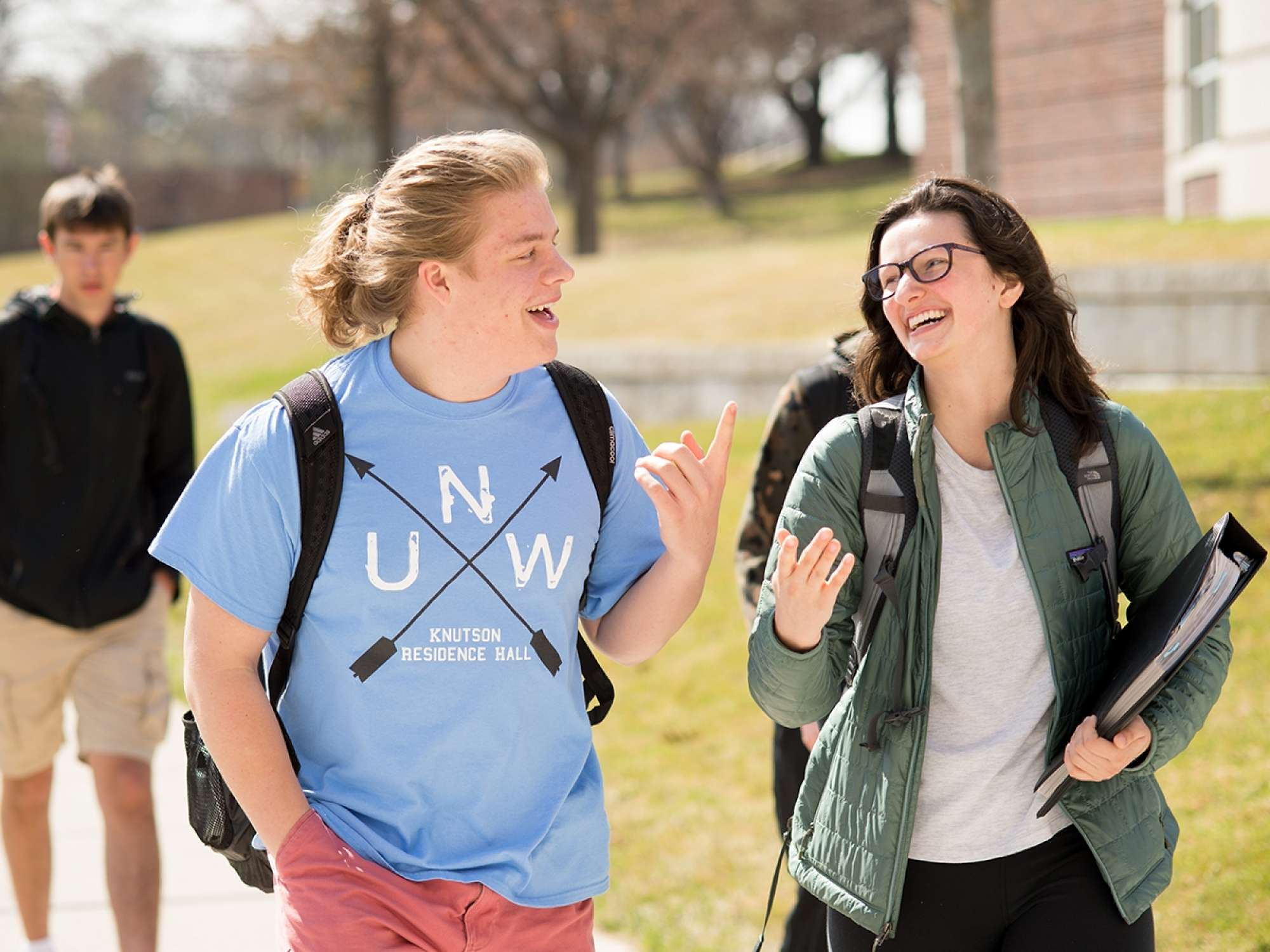 Two students walking together and laughing