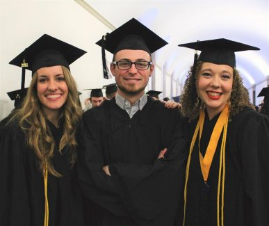 A man and two women graduating with public relation degrees from Northwestern