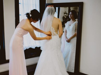 Bridesmaid helping bride adjust gown.
