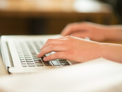 Student typing on computer